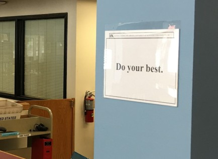 "An inspirational sign saying ""Do your best"" in a sign-holder next to the circulation desk"
