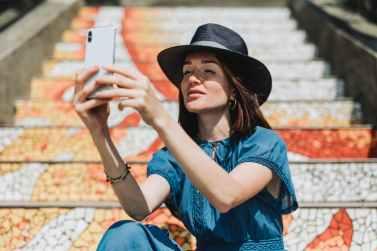 woman taking selfie beside concrete stairs