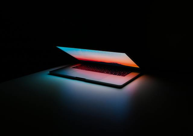 A laptop sits in the center of a dark room, partially open. The glare from the laptop is pink, blue, and white, and is the only light in the photo.